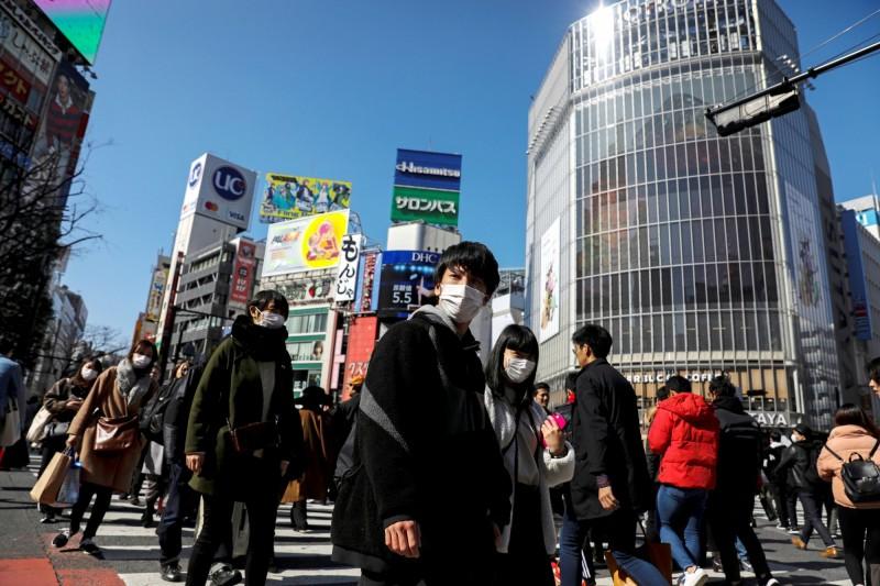 圖為日本澀谷街景,多數行人都戴著口罩自保。(路透)