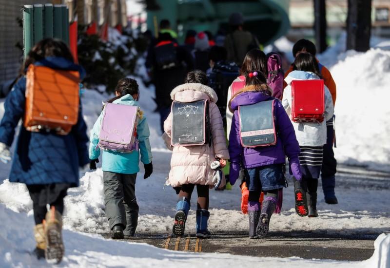 安倍晉三宣布全國高中小學3/2起暫時停課。圖為日本北海道札幌市的小學生。(路透)