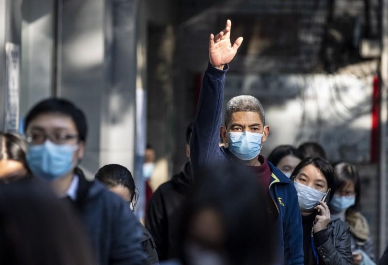 中國湖北省潛江市及浙江省寧波市今天分別公布「自主通報」及「舉報他人」獎金機制。圖為湖北省一名排口罩的男子舉起手。(歐新社)