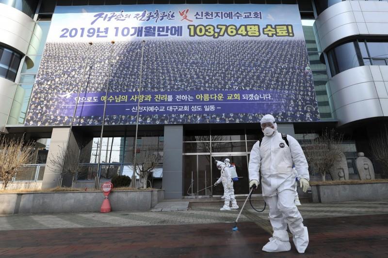 大邱市新天地教會1016名成員採檢結果出爐,其中833人確診感染武漢肺炎。圖為南韓防疫人員在大邱市新天地教會外消毒。(美聯社)