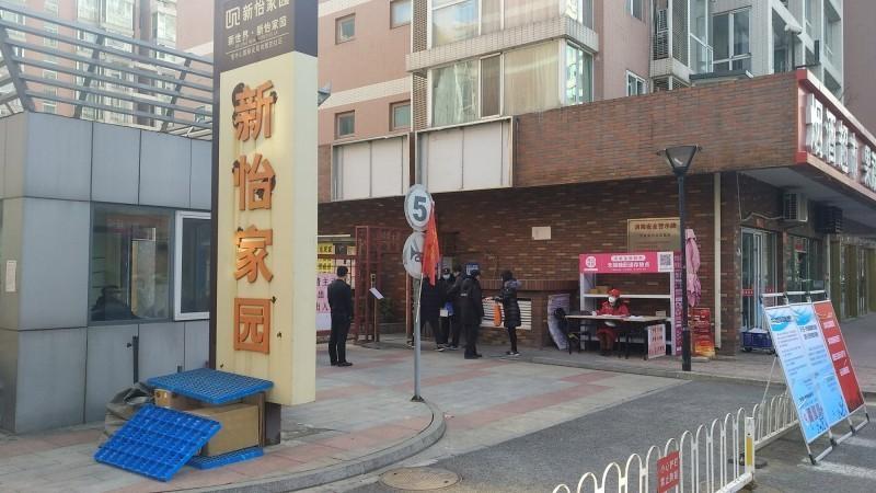 中國北京東城區新怡家園社區24日出現一名武漢肺炎確診病例,該名女子能在武漢封城回到北京,原因竟是刑滿出獄、家屬開車接回。圖為新怡家園北門的進出檢查站。(中央社)