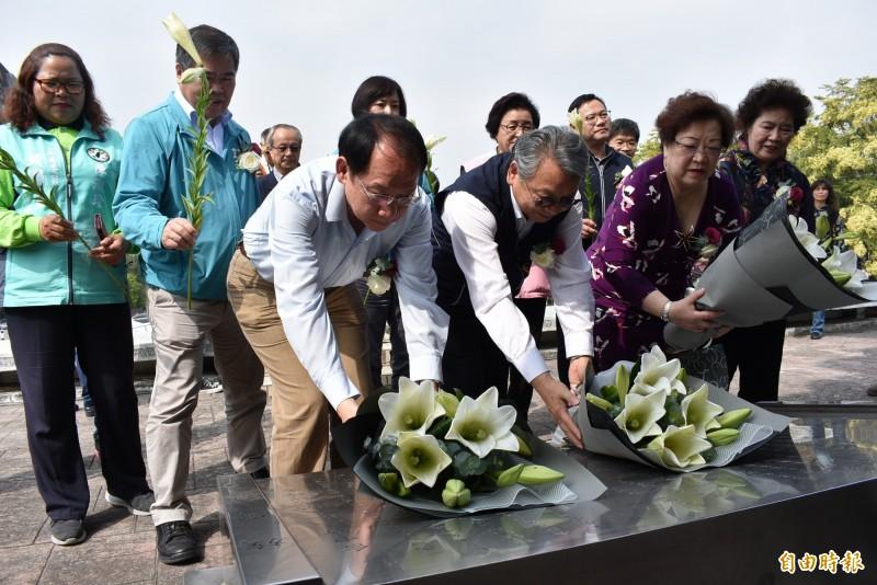 副市長令狐榮達(圖中)與遺族於紀念碑前獻花。(記者張瑞楨攝)