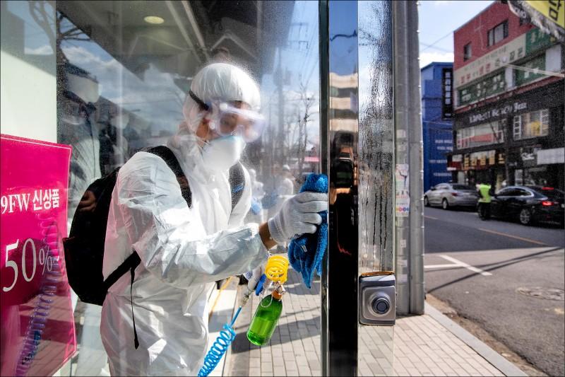 南韓首都首爾的文井洞羅德奧時裝街,亦見穿著防護衣的工作人員對商店大門仔細消毒。(彭博)