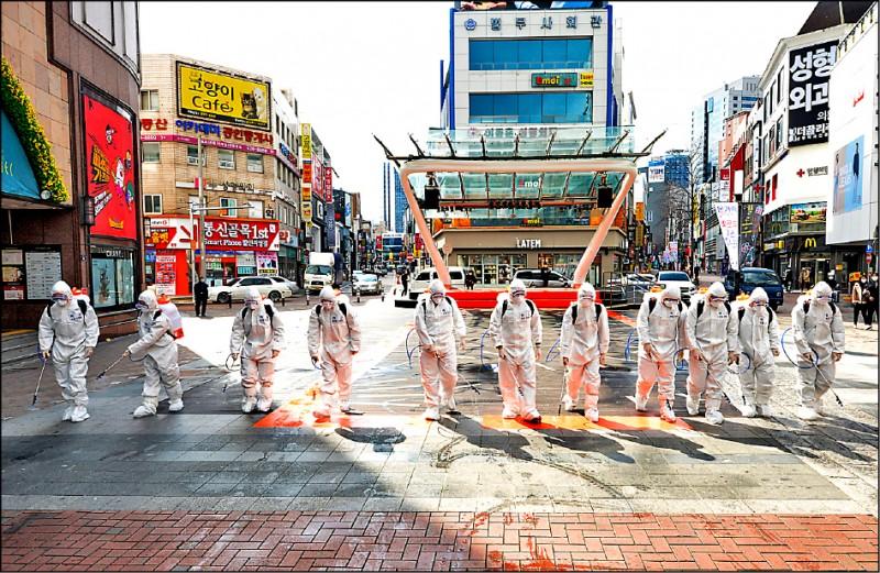 南韓軍人27日全副武裝入駐病例最多的大邱市,在街上噴灑消毒劑。(美聯社)