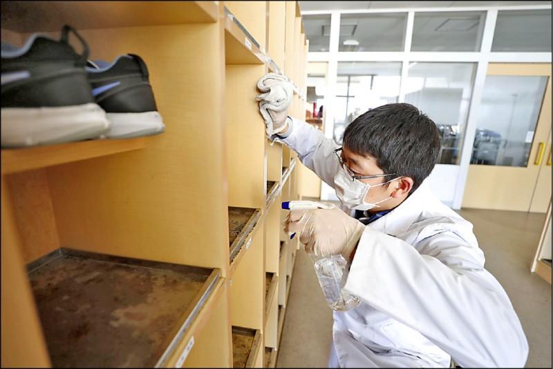 日本首相安倍晉三二十七日要求全國中小學及高中等學校,自三月二日起停課至四月春假結束。圖為工作人員二十七日在北海道北廣島市一所小學消毒。(路透)