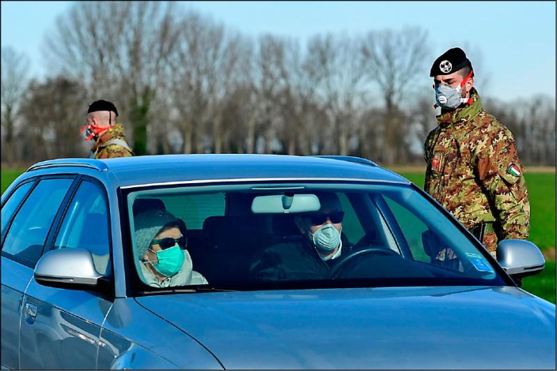 義大利軍人駐守在米蘭東南部卡斯蒂廖內達達鎮(Castiglione d'Adda)隔離區外的檢查哨,管控人員出入。(法新社)
