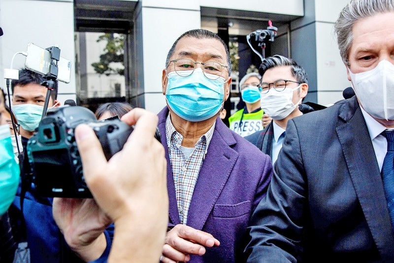 Publishing tycoon Jimmy Lai, center, leaves Kowloon City Police Station in Hong Kong yesterday.  Photo: AFP