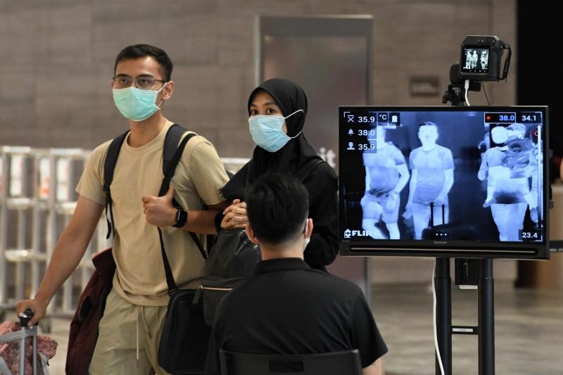 新加坡再增2起武漢肺炎確診,都是當地居民。圖為夫婦經過新加坡機場進行檢疫,非當事人。(法新社)