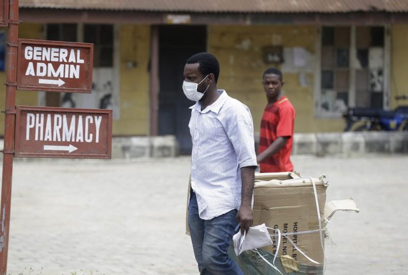 一名戴口罩的男子站在亞巴醫院外面,確診的義大利男子在此接受治療。(美聯社)