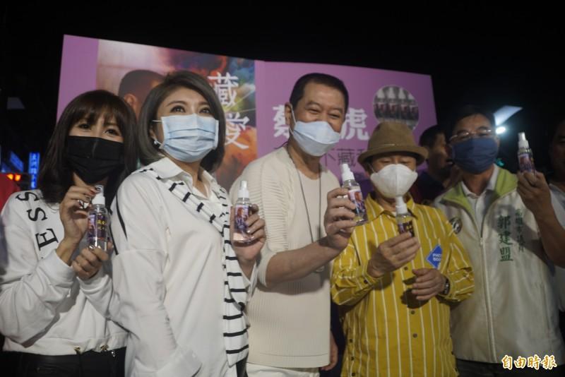 蔡小虎(中)、黃西田(右2)、陳思安(左2)等人今晚到六合夜市,發送消毒酒精給計程車司機和需要的民眾。(記者黃佳琳攝)