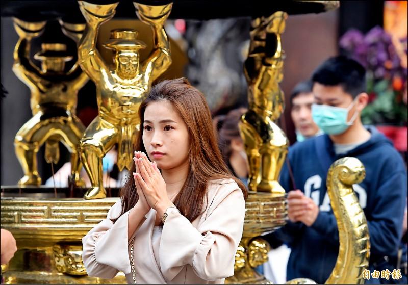 台北市艋舺龍山寺從3月13日起全面停止供香,信眾入內也不得自行攜帶香枝。圖為28日民眾參拜情形。(記者劉信德攝)