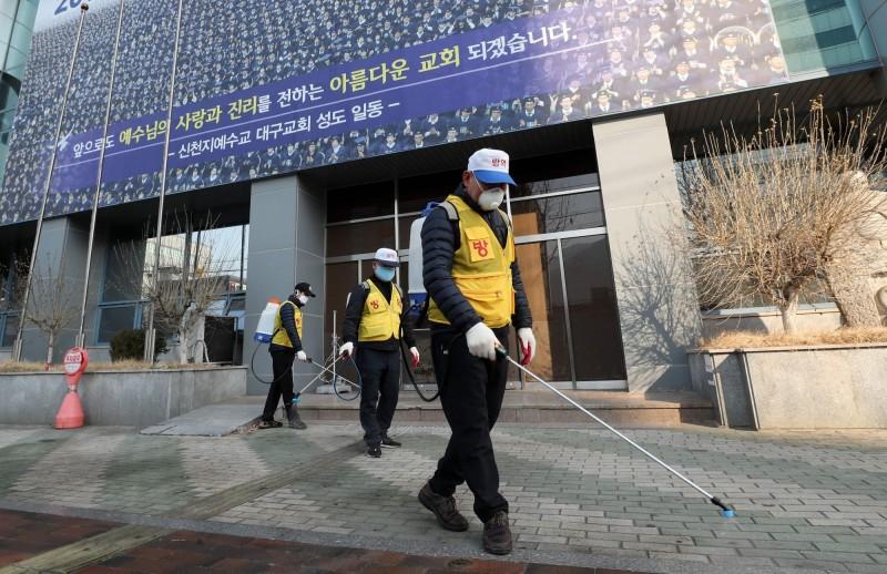 韓國新天地耶穌教會的21萬名信徒有17.1萬多人已接受調查,其中出現武漢肺炎症狀的3381人已採集檢體等待篩檢結果。圖為政府人員在新天地教會大邱教堂外進行消毒。(法新社)