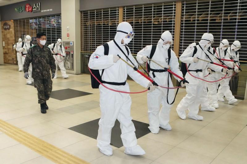 韓國首爾城東區政府1名41歲女職員曾和確診患者一起搭乘公寓電梯,當時2人都沒有戴口罩,但就僅僅只是在電梯內1分鐘的時間,該名女子事後就被驗出病毒陽性。圖為韓國公共場所消毒。(法新社)