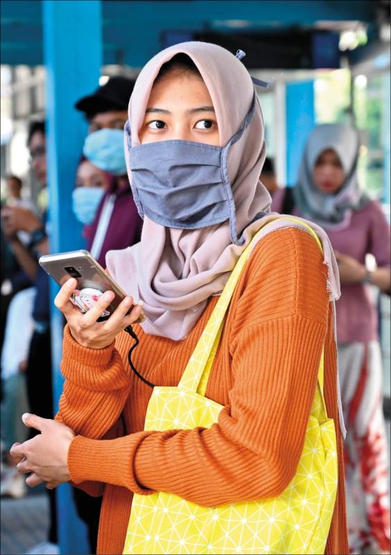 印尼二日證實國內爆發兩起武漢肺炎病例,雅加達一名女性戴著口罩上街。(法新社)
