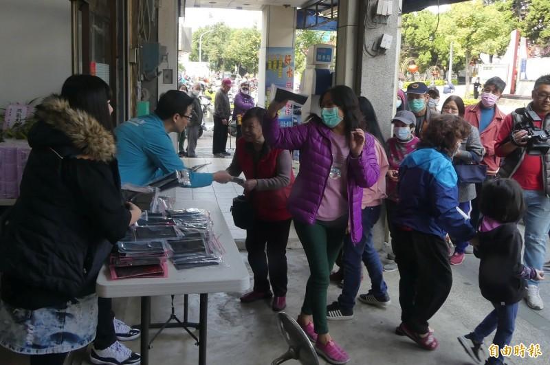 王中聖(左二)、王球球(左一)兄妹捐出團購庫存口罩贈送。(記者吳正庭攝)