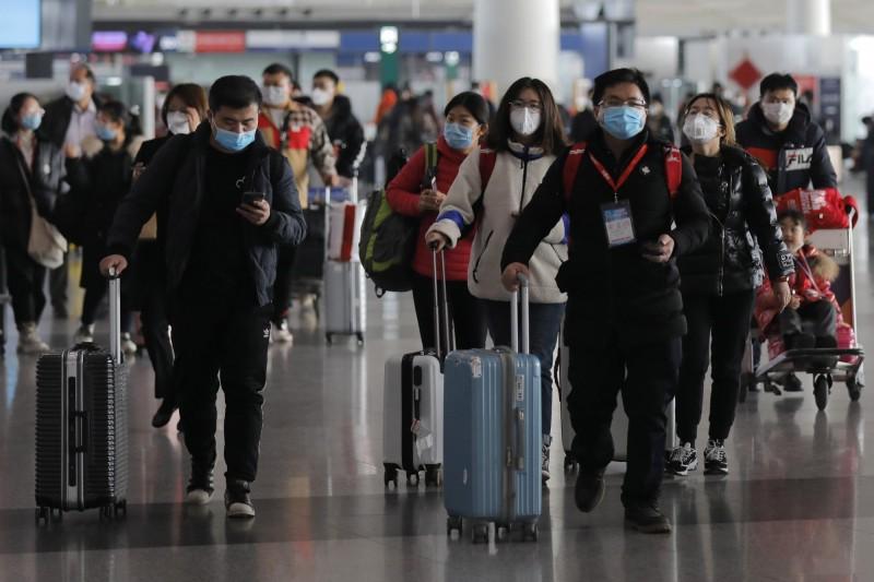 中國海關總署表示,截至今日凌晨0時累計有境外移入病例75例。圖為中國北京機場內戴著口罩的旅客。(歐新社)