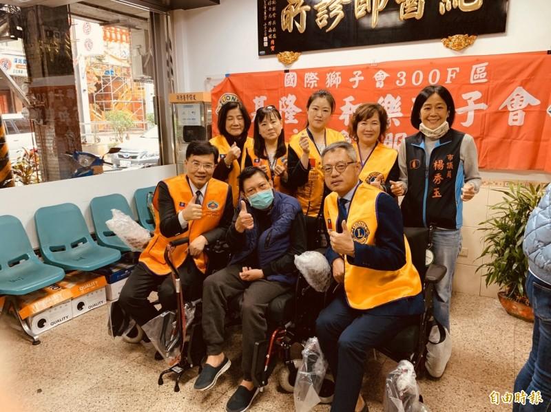 黃男(中)的家庭醫師紀乃正(前排左)媒合獅子會資源購置電動輪椅,方便黃男到醫院進行復建。(記者吳昇儒攝)