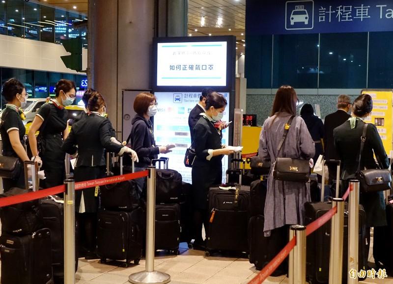 知名澳洲音樂家2日搭乘長榮航空班機返回澳洲後遭確診感染武漢肺炎,與音樂家同機的12名長榮空服員6日清晨返台,入境後搭乘防疫計程車離開機場。(記者朱沛雄攝)