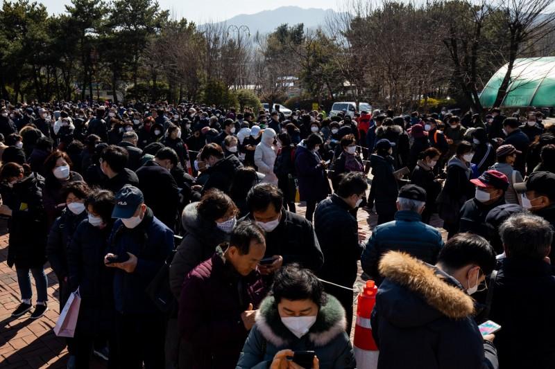 韓國口罩就算有錢還不一定買得到,目前青瓦台除了效法台灣推出實名制領口罩之外,還借鑑「我OK,你先領」運動,呼籲民眾把口罩禮讓給更需要的人。圖為韓國排隊買口罩的民眾。(彭博)