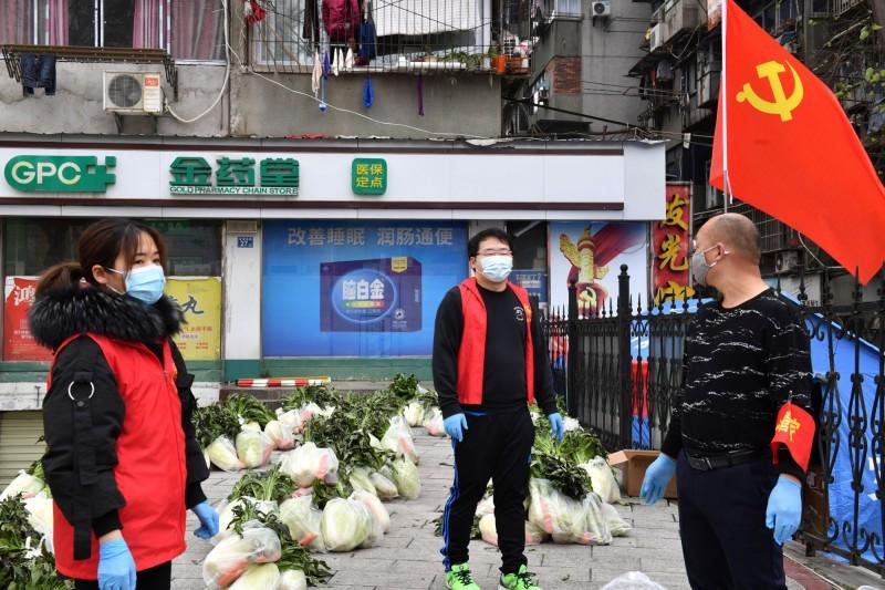 志工們等著分送蔬菜給社區居民。然而根據網傳的影片,許多居民抗議實際工作並不到位。(路透)
