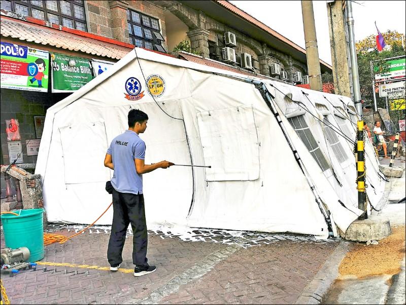菲律賓政府對其國內首次出現武漢肺炎的社區感染嚴陣以待,據信總統杜特蒂將宣布全國進入公衛緊急狀態。圖為一名防疫人員六日在菲國大馬尼拉地區的拉斯皮納斯(Las Pinas)市一家醫院外,正消毒用於隔離檢疫的帳篷。(歐新社)