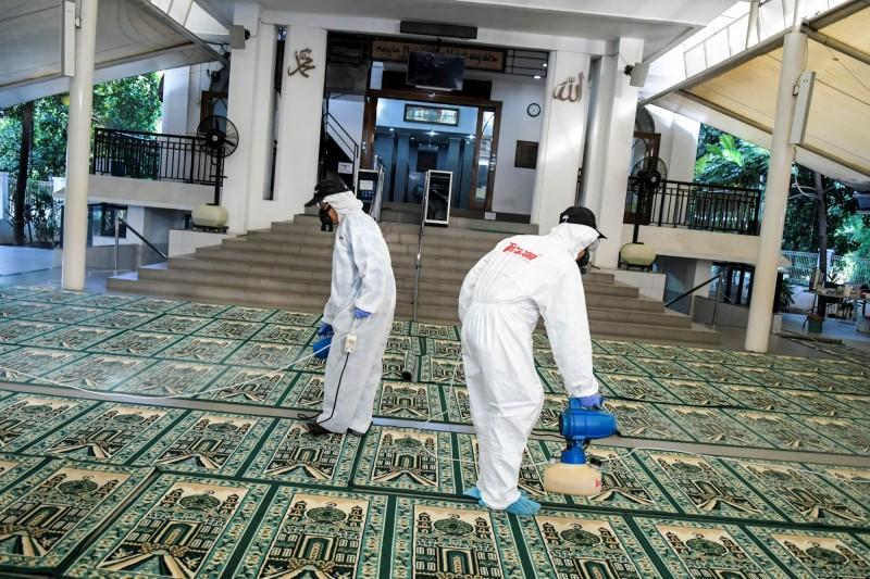 印尼今再傳兩名確診。圖為首起確診後,工作人員於清真寺內噴灑消毒水。(路透)