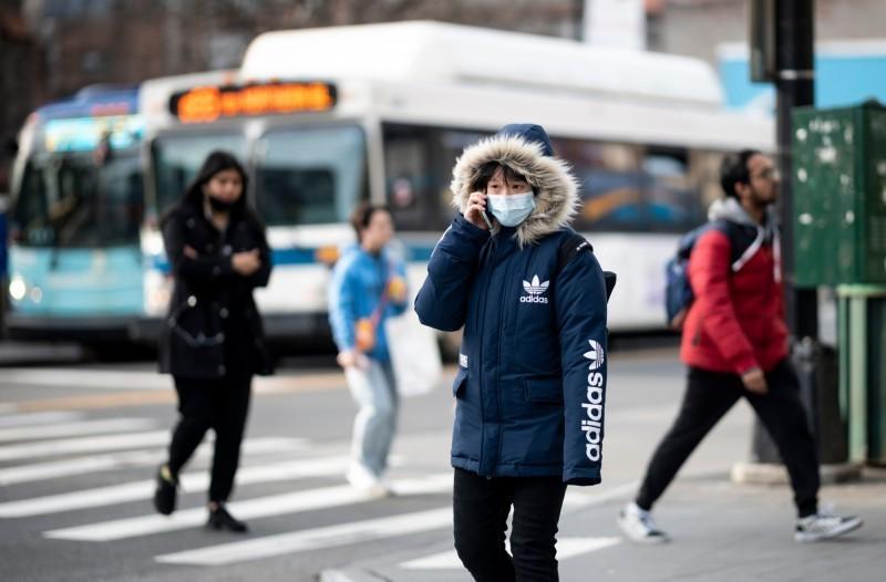 武漢肺炎(COVID-19)疫情持續在全球擴散,美國確診病例已突破400例,其中紐約州累計確診已達89例,7日也宣布進入緊急狀態。圖為美國街頭民眾配戴口罩。(法新社)