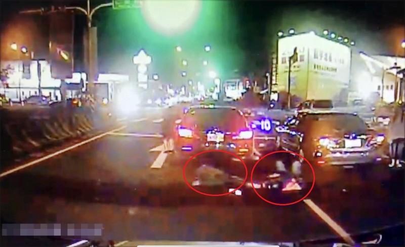 機車從後方連碰撞3部停等紅燈汽車,騎士(紅圈左)和後載乘客(紅圈右)倒地。(民眾提供)