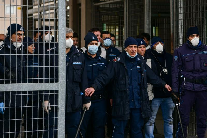 義大利當局為防止疫情擴散,禁止囚犯家屬探監。此舉引發多所監獄的囚犯憤怒,造反引發動亂,目前至少出現3死、多人受傷。圖為摩狄納監獄獄警在門口防守。(法新社)