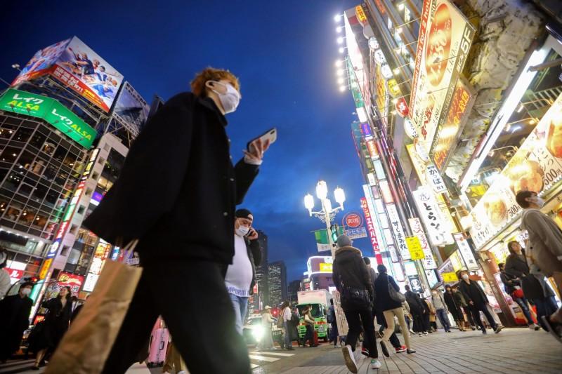 武漢肺炎疫情籠罩下,今夜的東京街頭燈火依舊輝煌,只是路人幾乎都戴著口罩,就怕病毒感染。(路透)