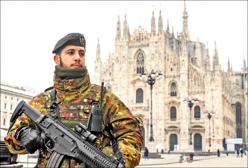義大利十日起全國封鎖、限制旅行,希望遏止疫情蔓延,圖為一名士兵十日駐守在米蘭大教堂前廣場。(路透)