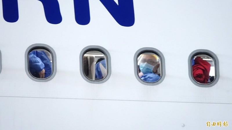 由機窗可看到機上旅客穿著防護衣裝備。(記者姚介修攝)