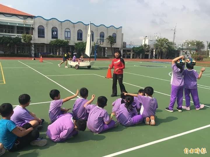 教練許瑞真(紅衣者)教導學生操作帆船技巧。(記者洪臣宏攝)