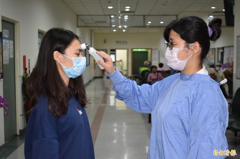 民眾到林新醫院就診入院後後在各門診區及進診間也必須量測體溫。(記者蔡淑媛攝)