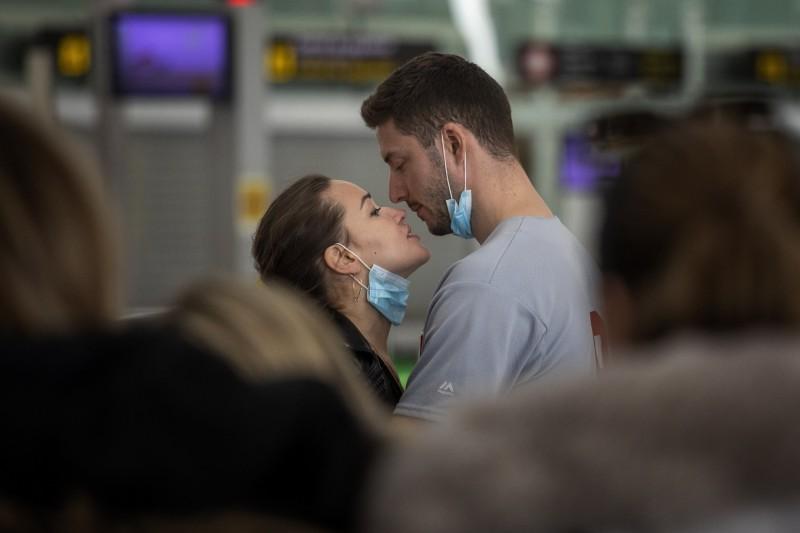 武漢肺炎疫情蔓延全球,西班牙12日發布官方聲明,病例一舉暴增828例確診、48例死亡,目前累積已達2968起確診、84起死亡病例,巴塞隆納市長已在家隔離遠端辦公。圖為一對在巴塞隆納機場的情侶。(美聯社)