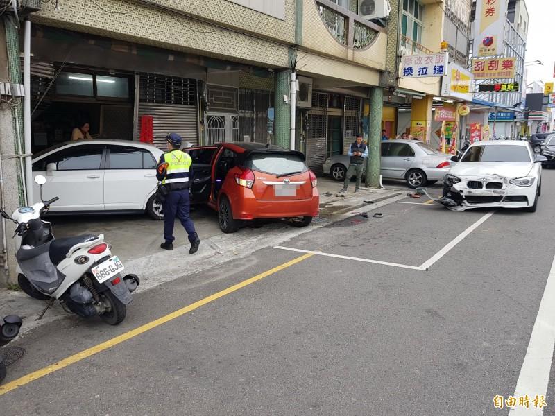 橘色小客車失控把停放在汽車停車格內的BMW「推走」,再撞擊到停放在民宅的白色小客車。(記者彭健禮攝)