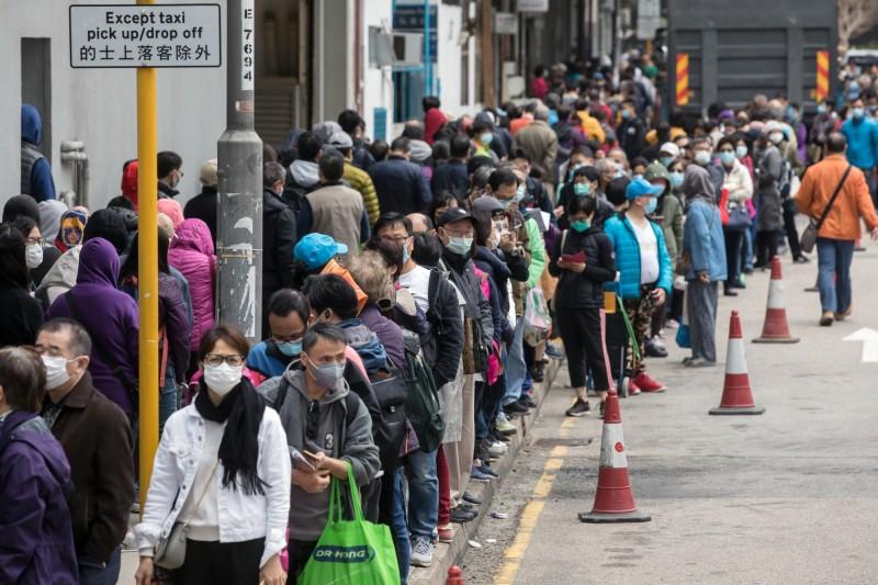 香港1名確診武漢肺炎的80歲老翁今(13日)病逝,成為香港的第4起死亡案例。圖為香港排隊購買口罩的人潮。(彭博)