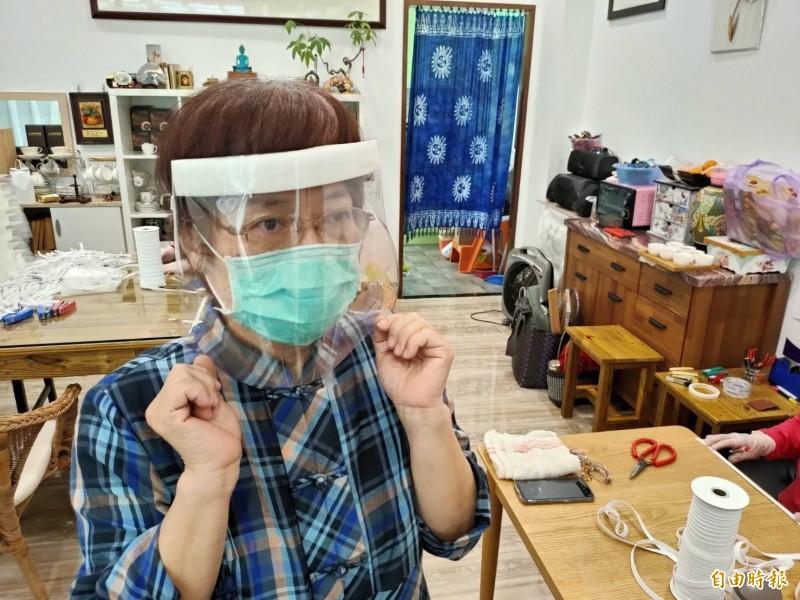 志工示範製作完成的防護面罩配戴方式,能擋住近距離的飛沫、檢體等物噴濺至眼口鼻。(記者佟振國攝)