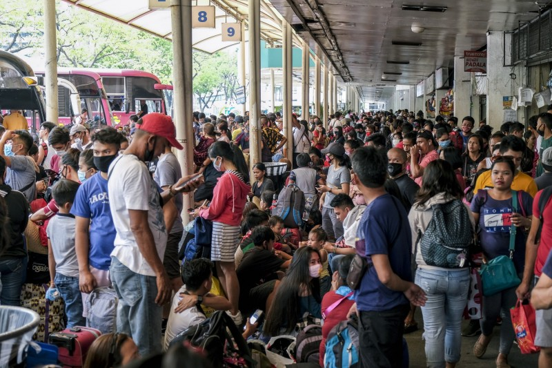 菲律賓武漢肺炎病例暴增,馬尼拉大都會發展局宣布,明天起一個月,每天晚上8時到隔天上午5時,將在大馬尼拉地區實施宵禁措施,圖為乘客在公車轉運站等待接運的畫面。(彭博)