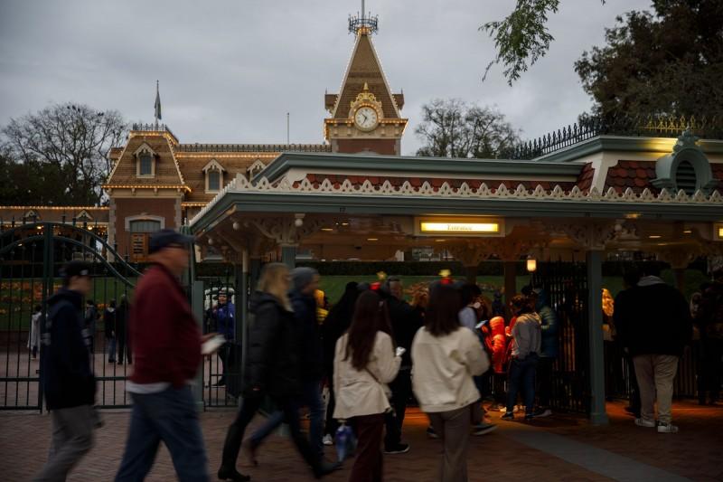 加州迪士尼(Disney)樂園因疫情於今(14)日暫時關閉,令人意外的是,開園最後1天,一早就湧入大批冒雨前來的遊客,直到下午人潮才逐漸散去。(彭博)