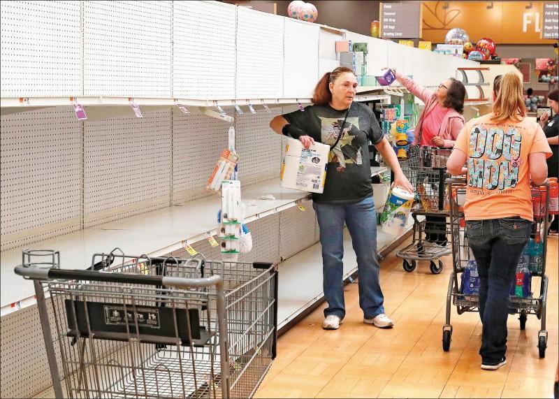 一名婦女十三日在美國馬里蘭州敦克爾克的一家超市拿走貨架上的最後一包衛生紙。新冠肺炎疫情被列為全球大流行外加美國全國進入緊急狀態,已引發恐慌性搶購潮。(法新社)