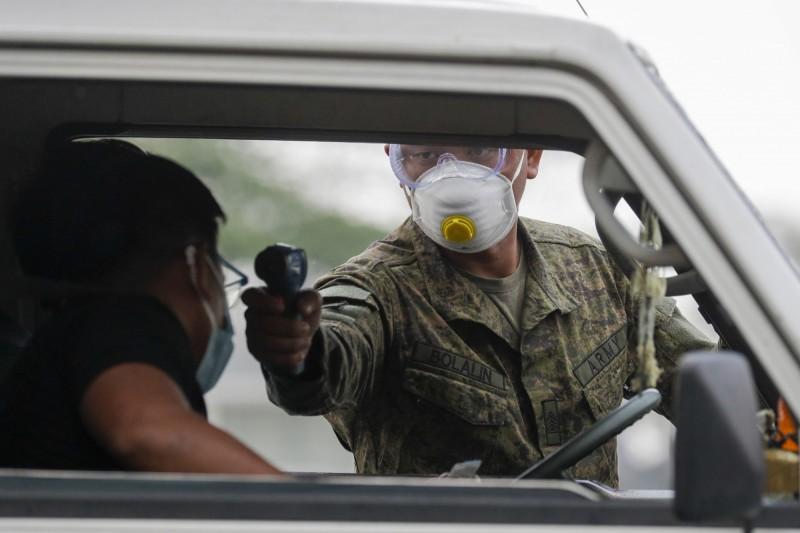 菲律賓奎松市(Quezon city)郊一名士兵逐一攔車檢查駕駛體溫是否異常。(美聯社)