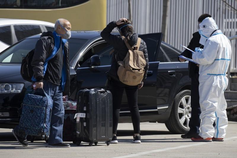 所有中國境外進北京的人員,強制隔離觀察14天,期間約新台幣2.8萬元的食宿費須自行負擔。圖為抵達北京的海外旅客。(美聯社)