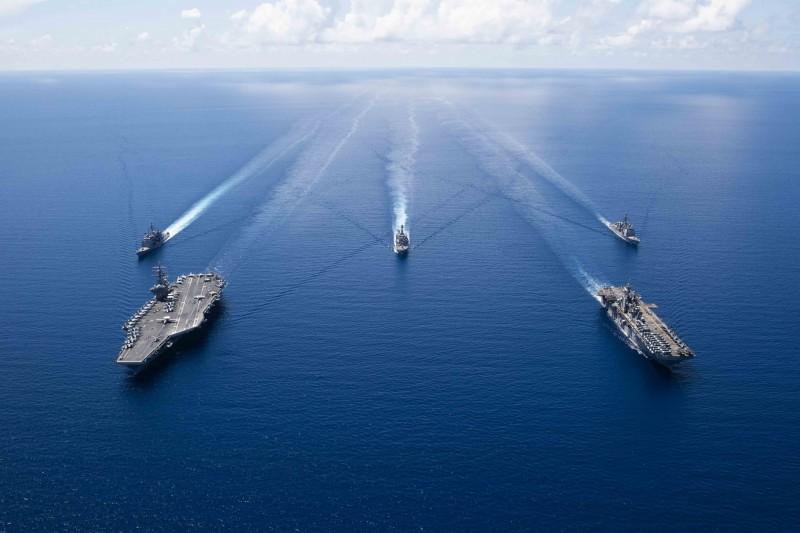 美國海軍黃蜂級兩棲突擊艦拳師號(USS Boxer LHD-4),在艦上服役的1名水兵被驗出新型冠狀病毒陽性。圖為拳師號(右)和雷根號航空母艦(左)及其打擊群共同航行。(法新社)