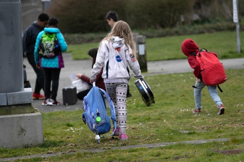 隨著武漢肺炎疫情擴散,美國50個州已有29州宣布關閉學校。圖為學校關閉後美國小學生們離校回家。(法新社)