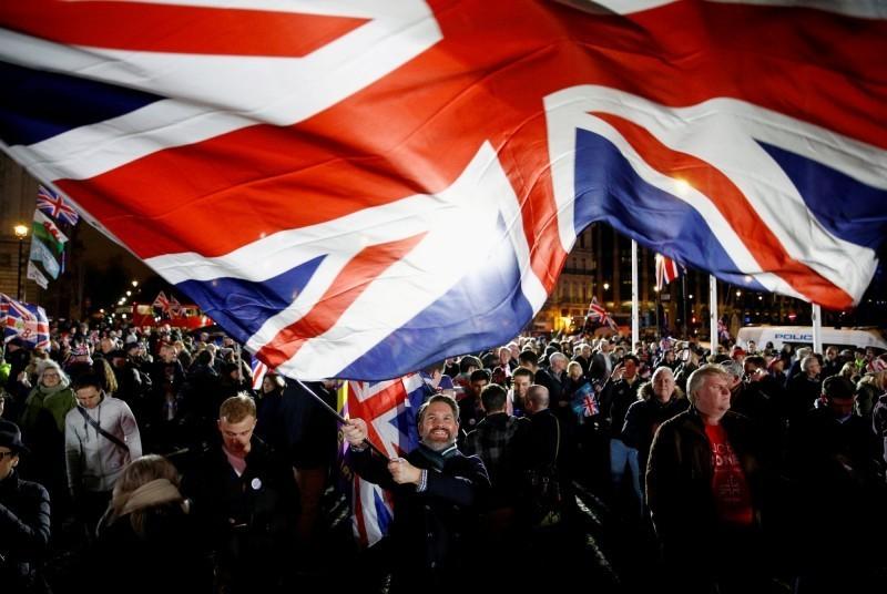 有英媒取得來自英國國家衛生署(NHS)一份內部文件顯示,評估未來12個月疫情會持續延燒,直到2021年春季,預估有80%的英國人遭到感染,其中更有15%(約莫790萬人)的人需要住院。。圖為英國民眾揮舞國旗慶祝脫歐。(路透資料照)