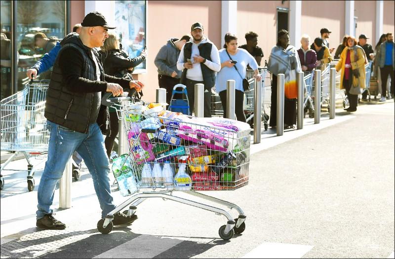 由於對疫情的恐慌,法國東北部城鎮厄奈姆(Hœnheim)民眾十六日湧入超市搶購民生物資。(法新社)