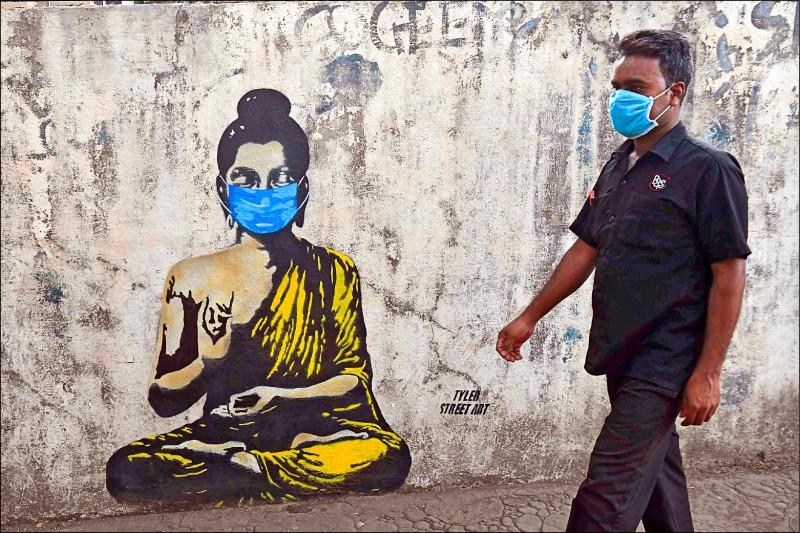 印度孟買民眾十六日行經戴著口罩的佛像塗鴉。(法新社)