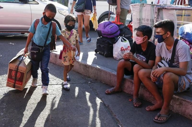 在馬尼拉家長陪同的學童戴起口罩等待接送(美聯社)。