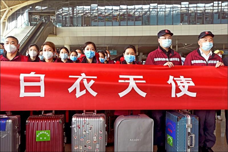 隨著中國疫情逐步好轉,一批從全國其他地區支援湖北抗疫工作的醫療人員,結束支援工作,十七日在武漢火車站搭車離開武漢前合影。(路透)